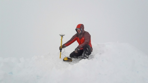 Scientist holding a measure tool in a snowy mountain top